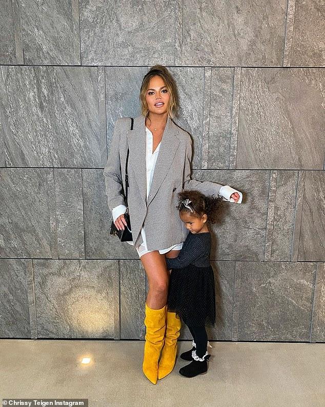 그것은 비즈니스를 의미합니다. 사진에서 젊은 Luna는 슈퍼 모델이 긴 흰색 탑, 회색 재킷 및 무릎 높이 부츠로 비즈니스 시크를 발산하면서 어머니의 다리에 매달 렸습니다.