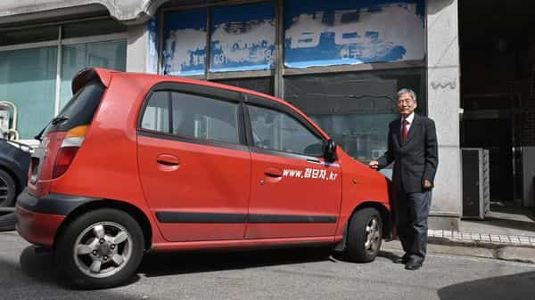 This picture shows retired South Korean professor Han Min-hong posing next to his 21-year-old self-driving car in front of his office in Yongin, south of Seoul. (AFP)