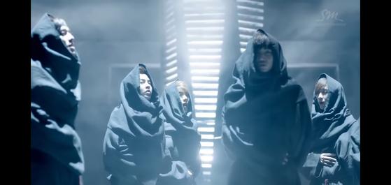 """엑소 데뷔 뮤직비디오 """"우리 엄마"""" (2012)를 연상시키는 로브를 입은 멤버들을 보여준다. """"중세 승려"""" 연세대학교 신학과 교수 Shamah J. Kunda에 따르면. [SCREEN CAPTURE]"""